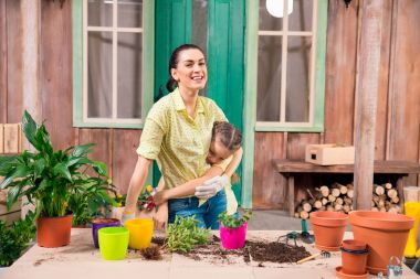 mother and daughter with plants and flowerpots standing and hugging at table on porch