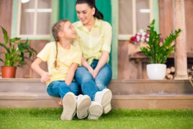 happy mother and daughter sitting on porch and hugging outdoors