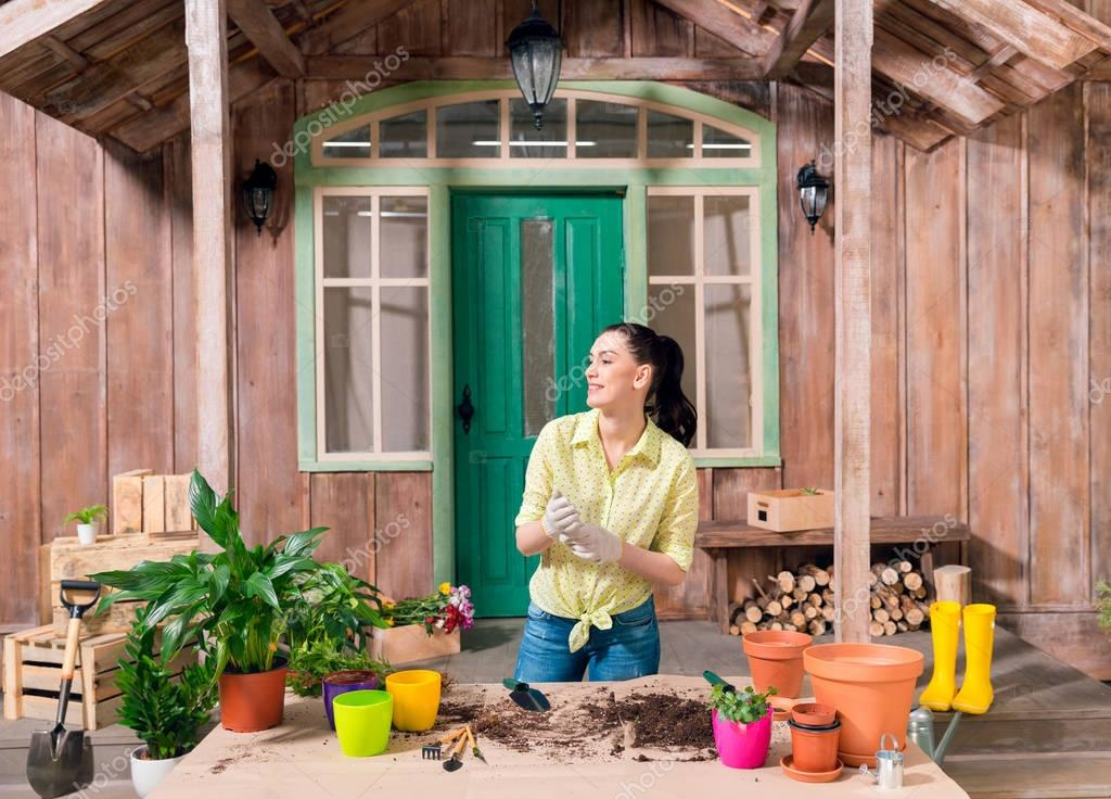 smiling woman with plants and flowerpots standing at table on porch