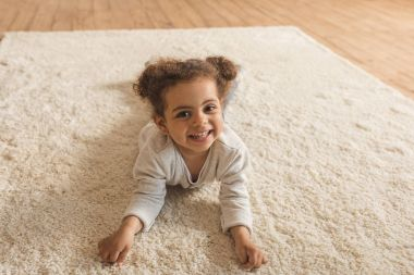 Adorable little african american girl lying on carpet at home stock vector
