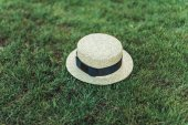 stylish straw hat with ribbon on grass