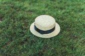 Stylový slaměný klobouk s mašlí na trávě