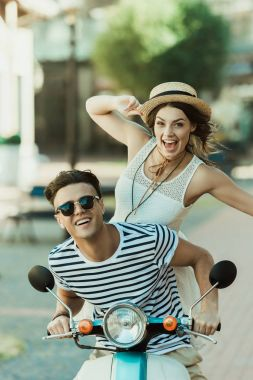 stylish couple riding moped