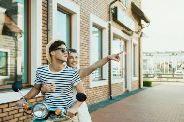Young smiling couple riding on moped