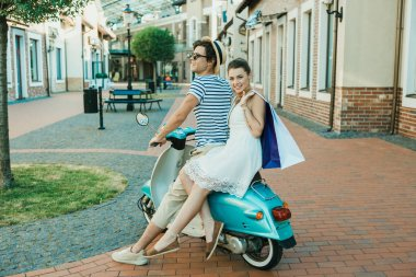 young stylish couple riding on scooter