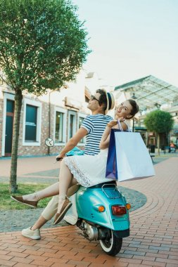 young casual couple riding on moped