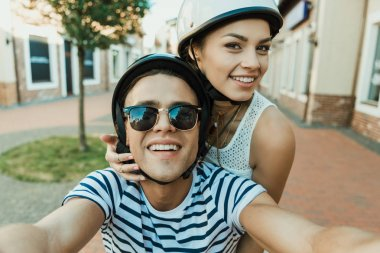 Young couple in helmets taking selfie