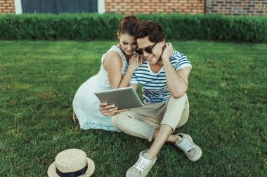 Couple using digital tablet at park