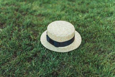 stylish straw hat with ribbon on grass