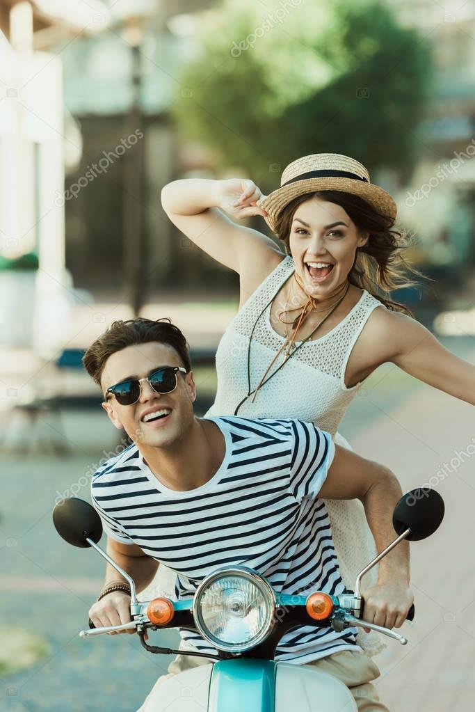stylish couple riding moped