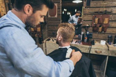 Handsome man with hairdresser at barber shop