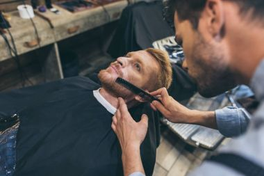 barber combing customers beard