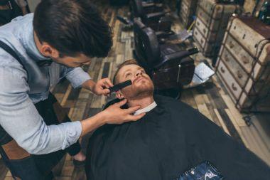 Male barber combing customers beard in barber shop stock vector