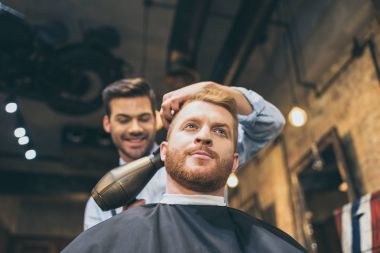 barber drying hair of customer