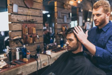 Handsome man getting hairstyle