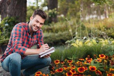 Smiling gardener with notebook in hands looking at camera in garden stock vector