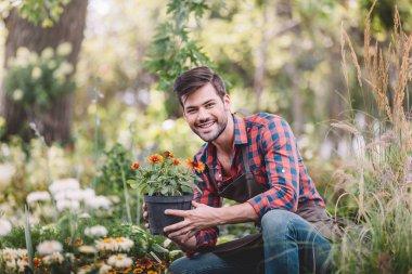 Portrait of smiling gardener holding flowerpot in hands and looking at camera in garden stock vector