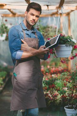 gardener with tablet in greenhouse