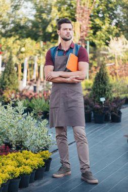 Pensive gardener in apron holding digital tablet in hand while standing in garden stock vector