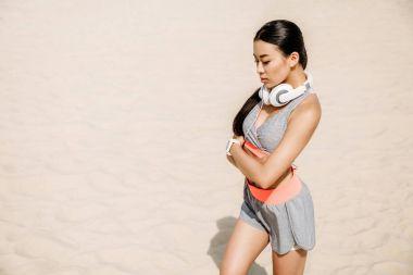 asian sportswoman with headphones
