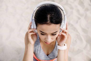 Beautiful asian woman with headphones listening music stock vector