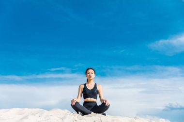 Asian woman meditating in lotus yoga pose on sand against cloudy sky stock vector