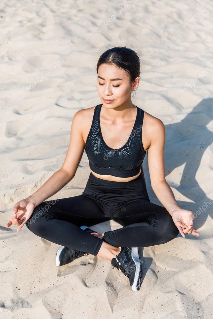 woman meditating on sand