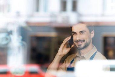 man in apron talking on smartphone