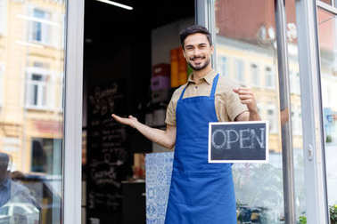 Small business owner holding open sign and smiling at camera stock vector