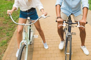 Couple with hands on bicycle handle bars