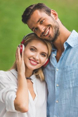 Smiling woman in headphones and boyfriend