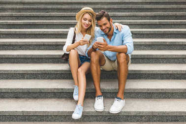 couple with smartphones on street