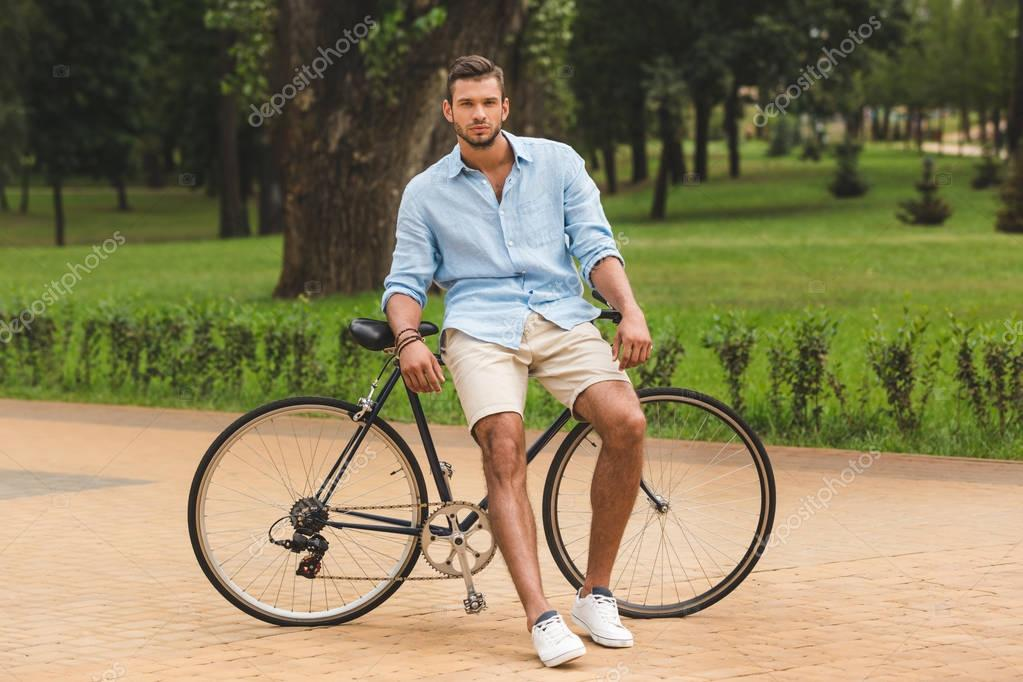 man with bicycle in park