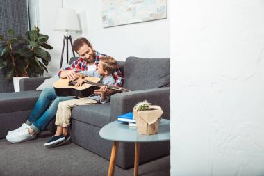 father and son playing guitar