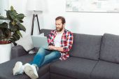 vousatý muž pomocí přenosného počítače