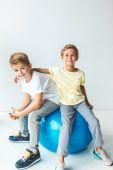 Photo boys sitting on fitness ball