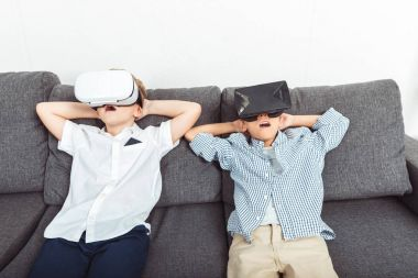 Shocked little boys using virtual reality headsets at home stock vector