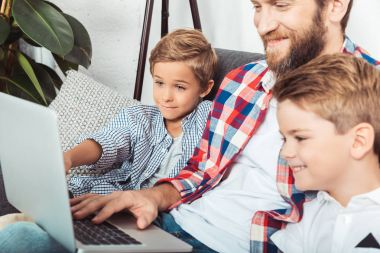 father with sons using laptop