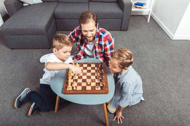 father with sons playing chess