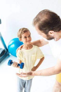 father and son training with dumbbell