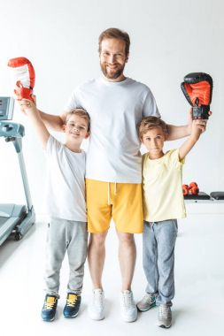father with sons in boxing gloves