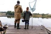 Fotografie otec a syn rybolov s prutem a čisté