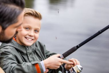 happy son fishing with rod