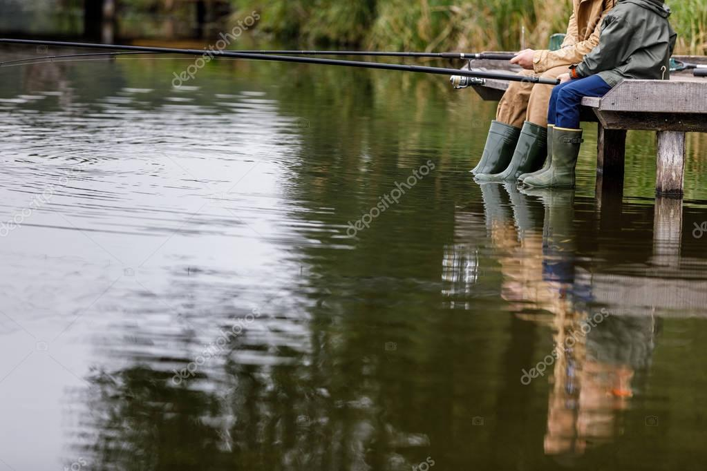 father and son fishing on lake