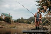 Fotografie muž rybolov s prutem u jezera
