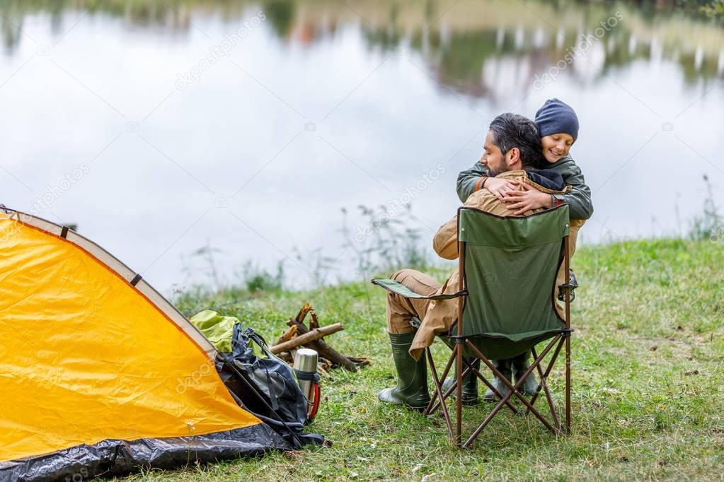 father and son hugging in camping