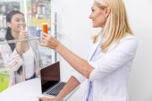 Fotografie pharmacist and customer in drugstore