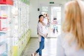 lékárník a těhotná žena v drogerii