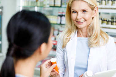 pharmacist giving medication to customer
