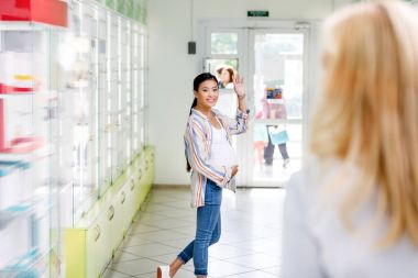 pharmacist and pregnant woman in drugstore